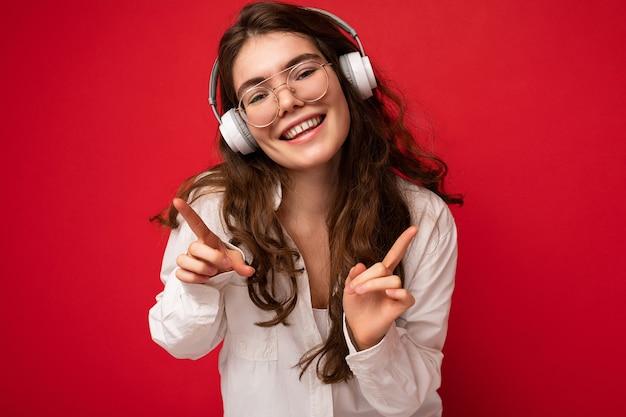 Foto del primo piano della giovane donna sorridente positiva attraente del brunet che porta camicia bianca e ottica