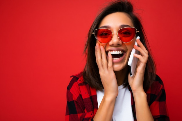 Foto del primo piano della giovane donna sorpresa positiva attraente che indossa t bianca alla moda della camicia rossa