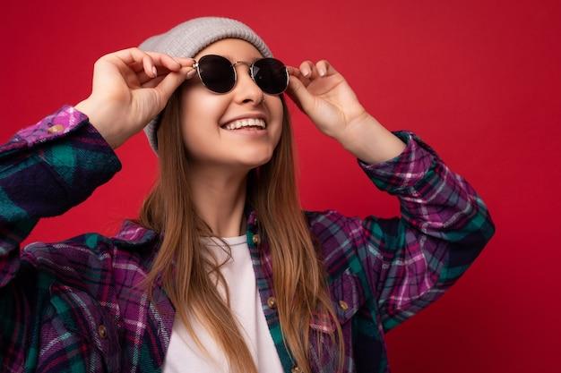 Foto del primo piano di una giovane donna bionda scura positiva sorridente attraente isolata su sfondo rosso che indossa una camicia elegante e colorata, cappello grigio e occhiali da sole che guardano in alto