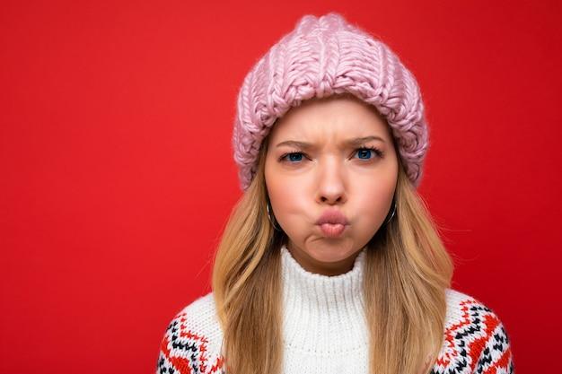 Foto del primo piano di bella giovane donna bionda arrabbiata divertente che sta isolata sopra la parete variopinta del fondo che indossa vestiti alla moda di tutti i giorni che guarda l'obbiettivo che mostra le emozioni facciali.