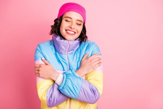 Foto del primo piano di bella signora che tiene le mani caldo cappotto colorato isolato sfondo rosa