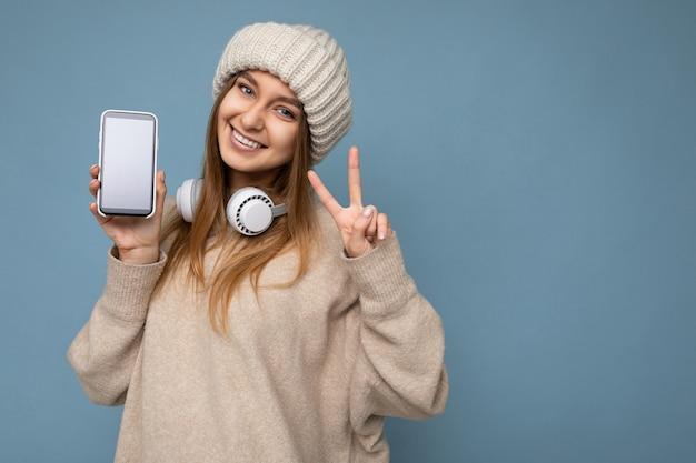 Foto del primo piano di bella giovane donna bionda scura sorridente positiva che indossa un maglione elegante beige