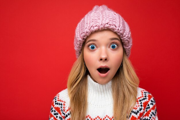 Foto del primo piano di bella giovane donna bionda stupita scioccata in piedi isolata sopra il muro di sfondo colorato che indossa abiti alla moda di tutti i giorni Foto Premium