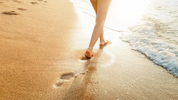 Primo piano di una bellissima giovane donna a piedi nudi che cammina nelle calme onde del mare caldo contro un tramonto incredibile