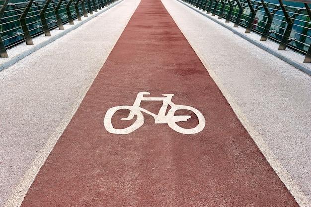 Foto del primo piano di un simbolo della bicicletta sulla pista ciclabile della città. segnale stradale della pista ciclabile sul ponte.