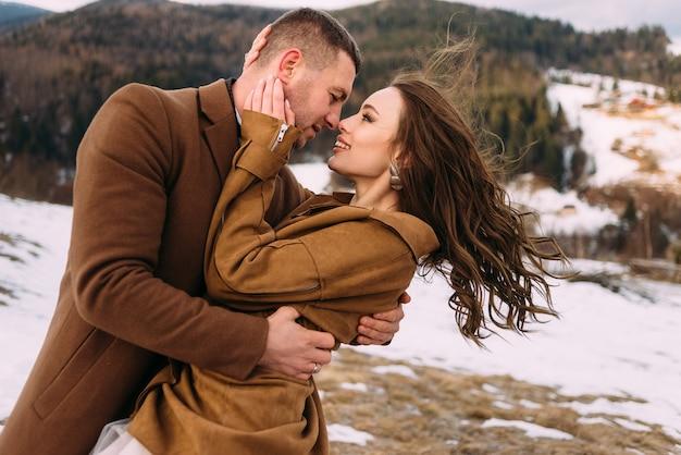 Foto primo piano di una sposa e lo sposo coccole sullo sfondo delle montagne invernali. gli sposi vestiti calorosamente si coccolano.