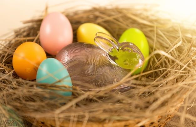 Primo piano di uova di pasqua colorate e coniglio di vetro sdraiato nel nido