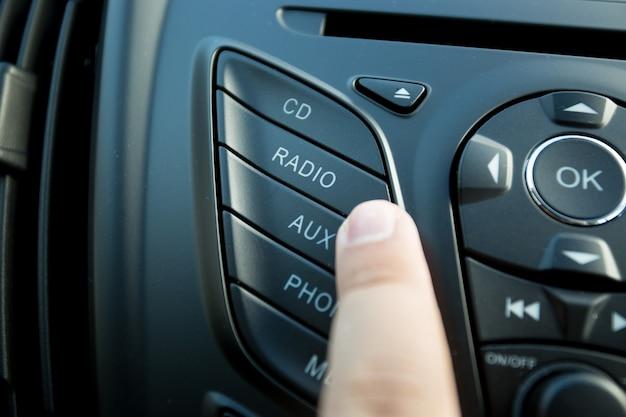 Primo piano del conducente che preme il pulsante radio sul cruscotto