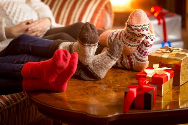 Primo piano delle gambe della famiglia in calzini di lana accanto al caminetto a natale