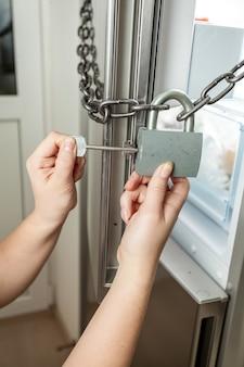 Primo piano della serratura di apertura femminile con catena sul frigorifero