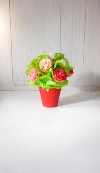 Primo piano del bouquet di fiori fatto di torte e cupcakes sulla scrivania in legno bianco. bellissimo scatto di dolci e pasticceria su sfondo bianco