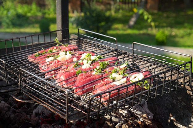 Primo piano di carne di manzo fresca con rosmarino e aglio su una griglia. bistecche alla brace su braciere con fumo naturale. concetto di cucina all'aperto.