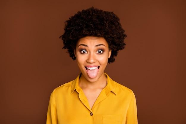 Foto del primo piano di divertente bella pelle scura signora ondulata positivo buon umore con la lingua fuori dalla bocca scherzare intorno indossare camicia gialla camicetta isolato colore marrone
