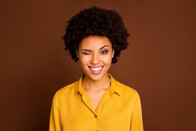 Foto del primo piano di divertente bella bella pelle scura signora ondulata positivo buon umore flirty lampeggiante un occhio indossare camicia gialla camicetta isolato colore marrone