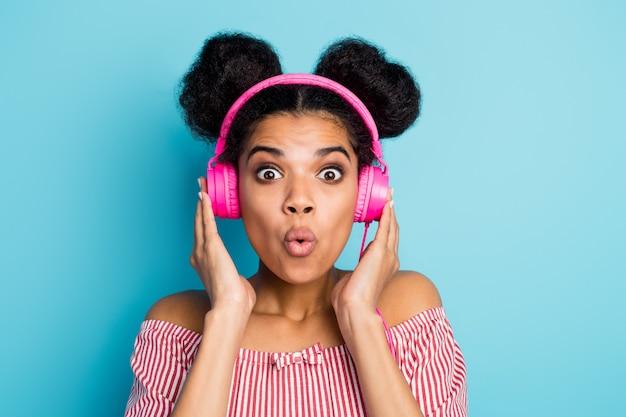 Foto del primo piano della signora pelle scura divertente ascolta musica auricolari moderni bocca aperta canzone preferita sulla radio indossare camicia a righe bianche rosse alla moda spalle spalle isolate colore blu muro