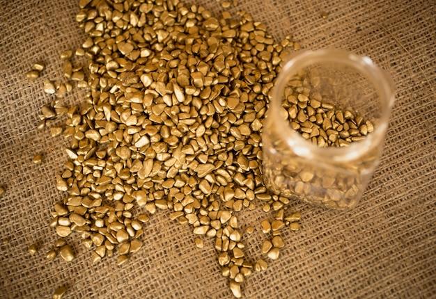 Primo piano di pepite d'oro e lingotti vuoti sdraiati su tela