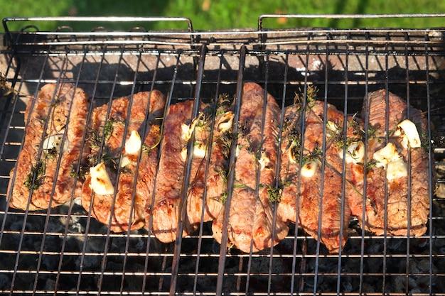 Primo piano di carne alla griglia con rosmarino e aglio su una griglia. bistecche alla brace su braciere con fumo naturale. cucinare all'aperto.