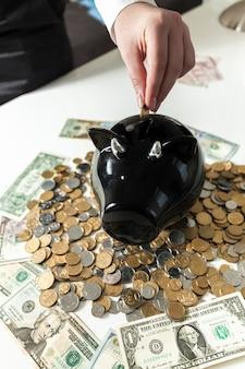 Foto del primo piano della mano che mette la moneta nel salvadanaio nero