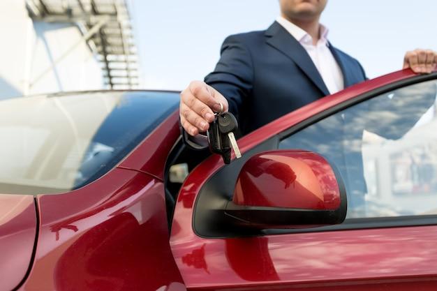 Primo piano di un bel venditore di auto che dà le chiavi