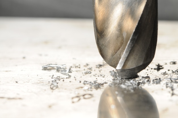 Foto del primo piano del processo di perforazione del foro, trucioli di metallo intorno al trapano.
