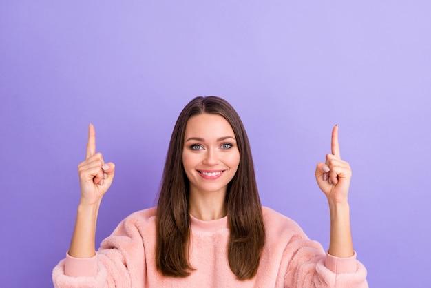 Foto del primo piano della signora che indica lo spazio vuoto del dito che dirige l'annuncio sulla parete viola