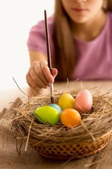 Primo piano della bambina che tiene il pennello e dipinge le uova di pasqua nel nido