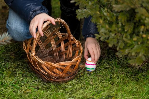 Primo piano della bambina che mette l'uovo di pasqua colorato nel cestino in