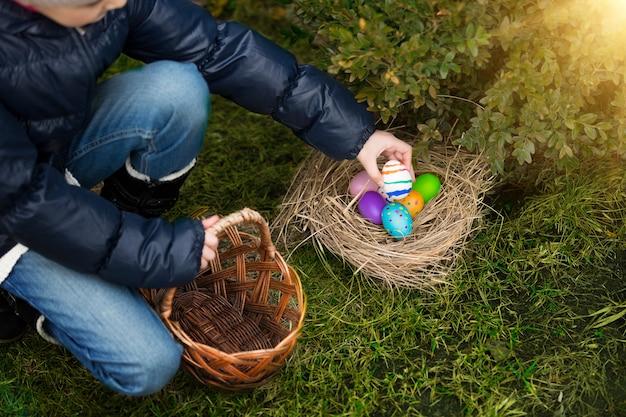Primo piano della bambina che mette l'uovo dipinto nel cestino
