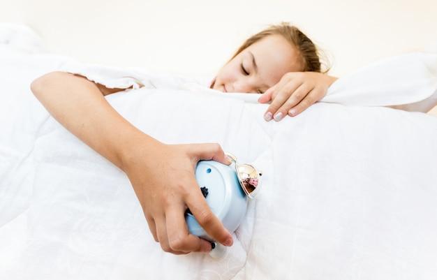 Primo piano della bambina che dorme e tiene la sveglia in mano