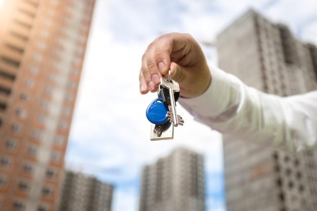 Primo piano della mano maschile che tiene le chiavi della nuova casa su edifici in costruzione