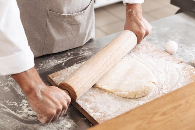 Foto del primo piano delle mani maschii che producono pasta per pasticceria con il mattarello di legno, sul tavolo al forno o in cucina