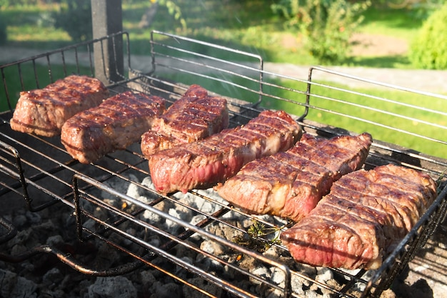 Primo piano di media carne alla griglia su una griglia. bistecche alla brace su braciere con fumo naturale. cucinare all'aperto.