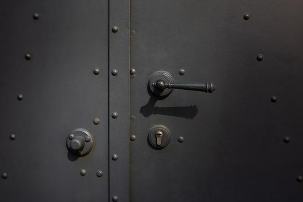 Primo piano di una porta di metallo con maniglia e serratura
