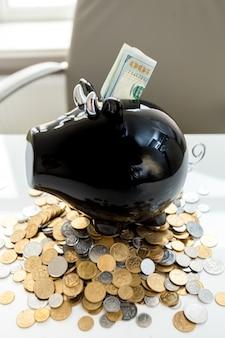 Primo piano del salvadanaio su un mucchio di soldi con dollari nello slot