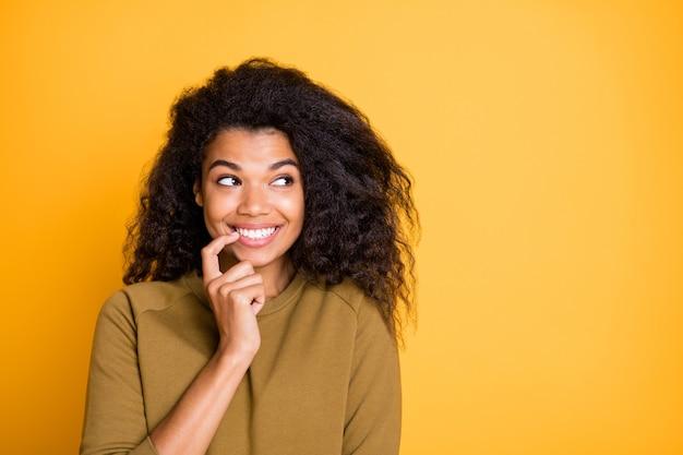 La foto del primo piano della signora della pelle piuttosto scura sciocca umore infantile guardando lo spazio vuoto laterale ha fatto cosa complicata mordere il dito indossare pullover casual isolato su sfondo di colore giallo