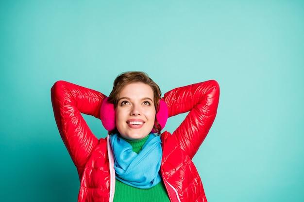 Foto del primo piano della bella signora godersi la giornata invernale cercare lo spazio vuoto stelle vista le mani dietro la testa indossare casual cappotto rosso sciarpa rosa paraorecchie isolato verde acqua muro di colore