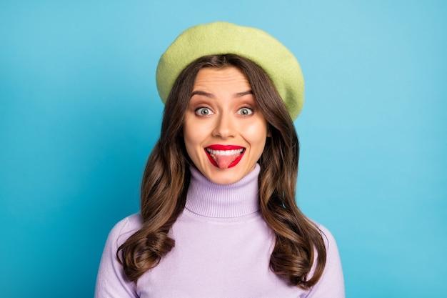 Foto del primo piano della bella signora con la lingua fuori bocca buon umore labbra rosse persona infantile indossare cappello berretto verde dolcevita viola isolato parete colore blu