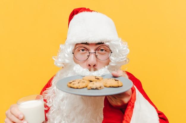 Foto del primo piano di babbo natale che sente l'odore dei gustosi biscotti al cioccolato