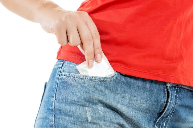 Foto del primo piano della giovane donna sexy che prende il preservativo dalla tasca