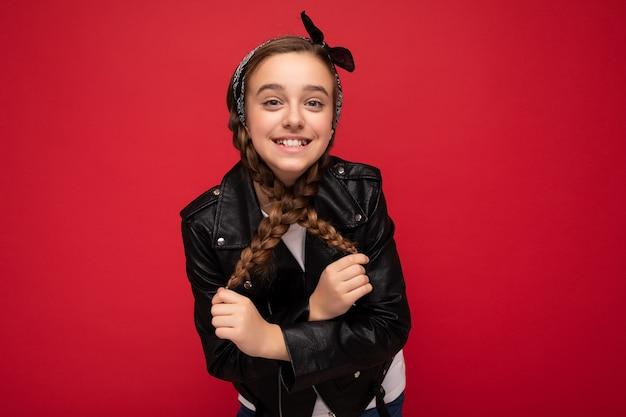 Foto del primo piano colpo di bella bambina bruna sorridente felice con le trecce che indossa giacca di pelle nera alla moda