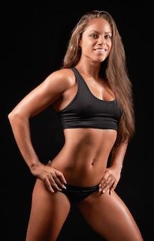 Foto del primo piano di un ritratto di donna sportiva che indossa abiti sportivi neri nel buio