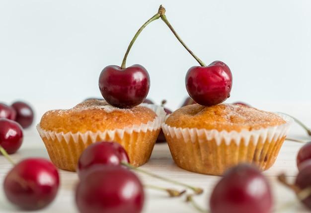 Primo piano di due muffin decorati da una coppia di ciliegie. concetto di romanticismo