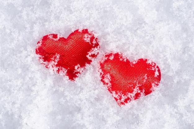 Primo piano di due cuori di stoffa rossa su una neve bianca