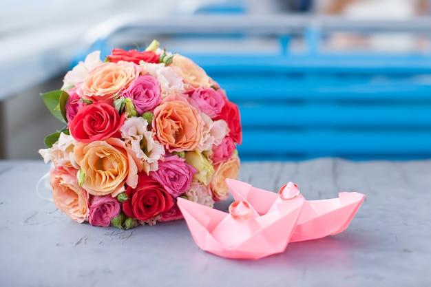 Foto del primo piano di due anelli e bouquet di nozze d'oro