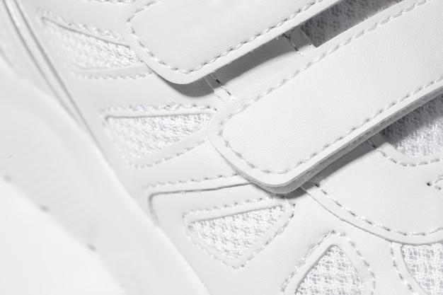 Una foto in primo piano della chiusura in velcro delle scarpe da ginnastica foto macro di scarpe da ginnastica bianche sportive per bambini ma...