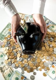 Foto del primo piano della donna che tiene salvadanaio di maiale nero su una pila di monete
