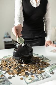 Primo piano di una donna che inserisce un dollaro nel salvadanaio di un maiale