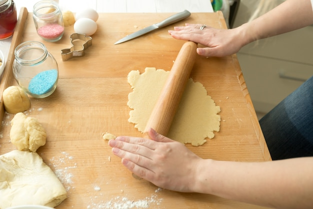 Primo piano della donna che prepara l'impasto per i biscotti su una tavola di legno