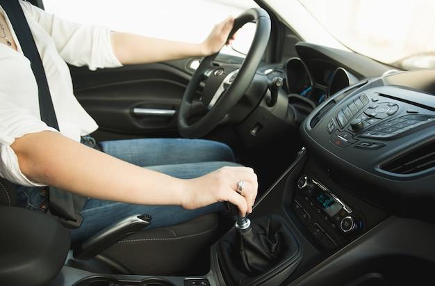 Primo piano della donna che cambia la leva del cambio e guida un'auto