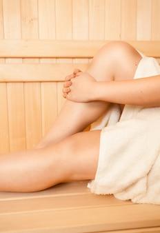 Primo piano della donna che tocca i piedi sulla panchina della sauna